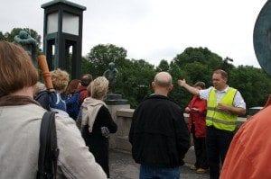 Jakob Idland i grønn vest er en inspirert og dyktig guide hos HMK Sightseeing. Han forteller levende om Vigeland på både engelsk og tysk og turistene ler mye.