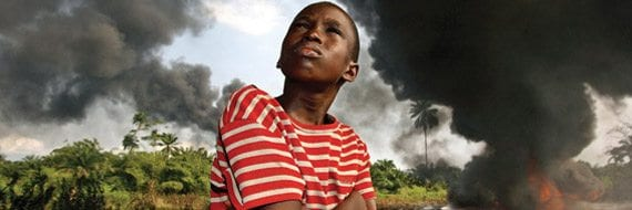 An Ogoni boy looks up at the black smoke pouring from a Shell oil pipeline that has been burning for weeks in Kegbara Dere, near the oil rich city of Port Harcourt. The fire burned furiously for months blanketing the village with black smoke and ash that ruined the farmer's fields. Foto: George Osodi.
